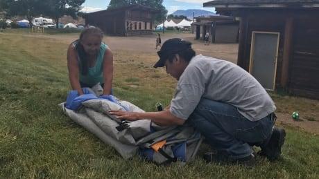 Evacuees pack up tent
