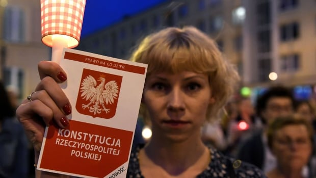 A woman holds a candle as protesters take part in a demonstration in front of the Polish Supreme Court on Sunday in Warsaw to protest against the new bill changing the judiciary system.