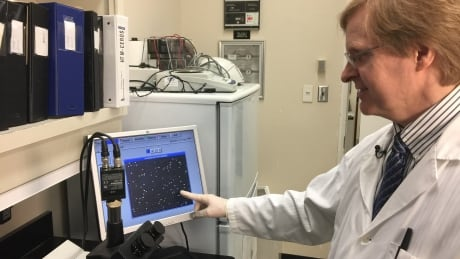 Dr. Keith Jarvi looking at sperm sample