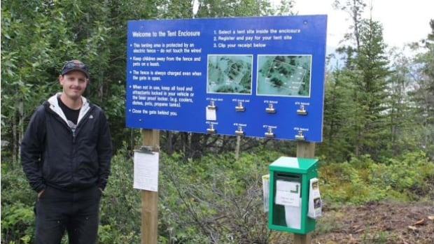 Research assistant Brandon Drost stands beside a sign explaining how to use the tent area inside the electric fence.