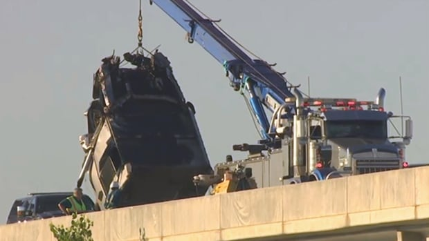 The cab of a semi-trailer that crashed Wednesday morning is hauled up from the floodway.