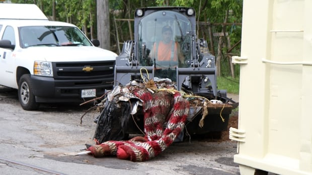A city worker removes a comforter and other items from the Stuart Street property.