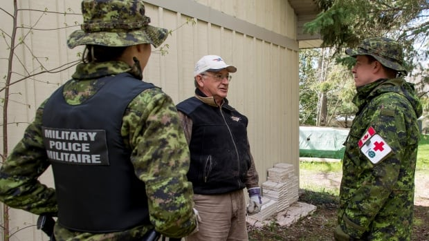 A member of the military police and a medical technician gather information from a resident of one of the flooded areas in Aylmer, Que., in May. Enforcement of certain provincial laws fall outside the authority of military police, as do certain traffic safety provisions.