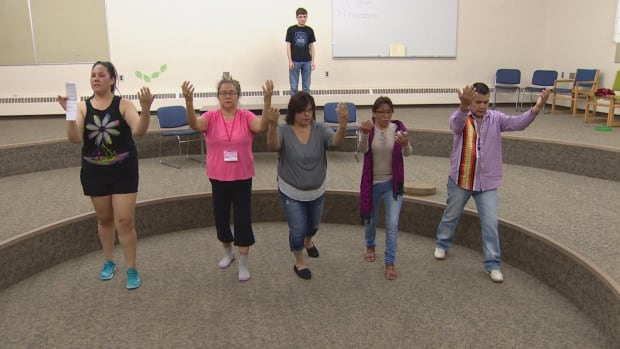 Students at the Canadian Indigenous Languages and Literacy Development Institute perform a seven-point prayer before beginning their play.