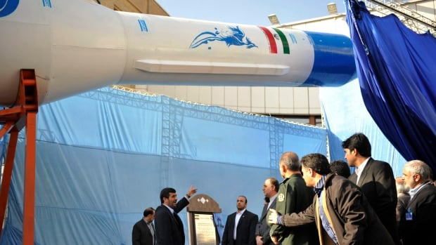 Mahmoud Ahmadinejad, centre, who was Iran's president from 2005 to 2013, gestures toward a model of Iran's new domestically built light booster rocket, named Simorgh, in Tehran on Feb. 3, 2010.