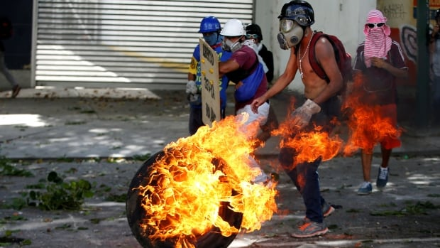 Demonstrators use a tire on fire to block a street at a rally during a strike called to protest against Venezuelan President Nicolas Maduro's government in Caracas, Venezuela on Wednesday.