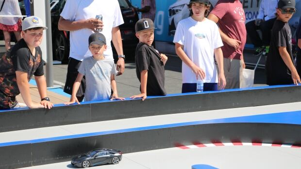 Boys waited their turn to drive a remote-controlled car around a miniature race course at the Allianz eVillage at the Montreal ePrix electric car race on Saturday.
