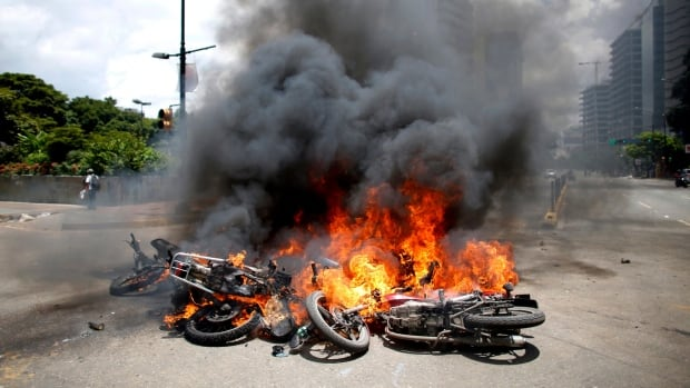 Motorcycles burn after an explosion during clashes in Caracas Sunday. The explosion injured several security officers and damaged several of their motorcycles. The officers were then seen throwing the privately owned motorcycles into the remaining fire in reprisal.