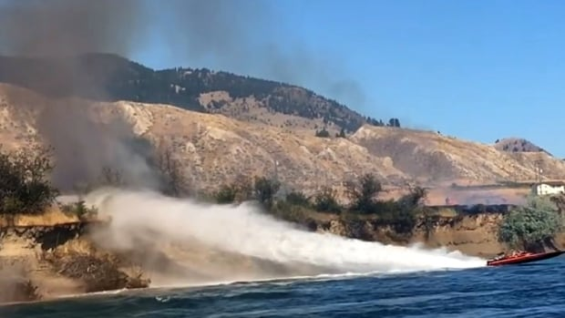 Koyne Watson and Tasha Hunt tried to blast a grass fire with their jetboat's spray along the banks of the Thompson River, near East Shuswap Road.