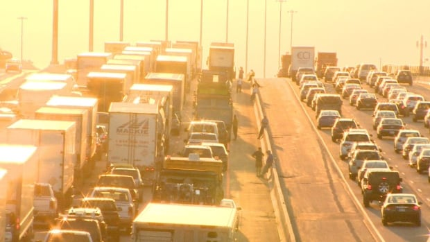 Commuters stand on Highway 401 after a fatal truck fire early Monday led to a series of lane closures.