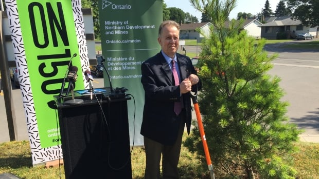 Michael Gravelle, Ontario's minister of northern development and mines stands beside an Eastern White Pine sapling he planted Monday in Thunder Bay.