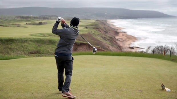 A golfer hits from the tee on the 528-yard par 5 18th hole at Cabot Cliffs. SCOREGolf named it the best public course in Canada for 2017.