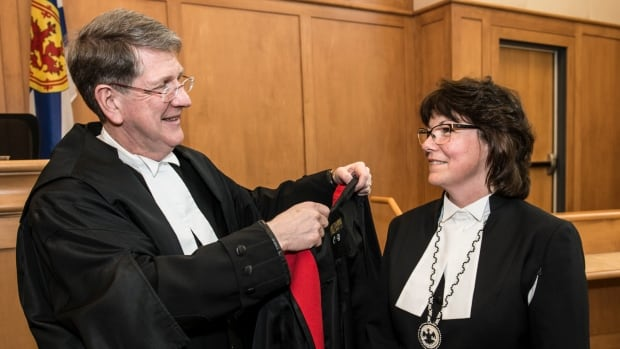 Nova Scotia Chief Justice Michael MacDonald, of the Nova Scotia Court of Appeal, places a robe on Catherine Benton, the province's first female Mi'kmaq judge, at a ceremony in March. Benton sits in provincial and family courts.