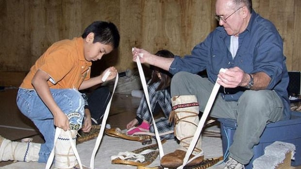 Pat Bobinski ties snowshoes with a youth. Bobinski coached biathlon in the Northwest Territories - both ski and snowshoe - for more than 40 years.
