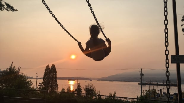 A child swings at a park in East Vancouver at sunset on Tuesday night, before smoke that had lingered at higher elevations moved lower Wednesday, reducing air quality.