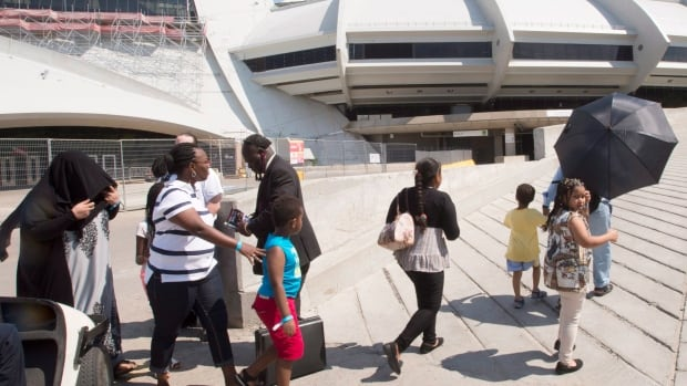 A group of asylum seekers leave Olympic Stadium to go for a walk in Montreal on Wednesday. The stadium is being used as temporary housing to deal with the influx of asylum seekers arriving from the United States.