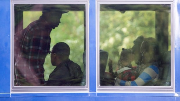 Asylum seekers board a bus after crossing the border into Canada from the U.S. at a police checkpoint close to the Canada-U.S. border near Hemmingford, Que., on Thursday.