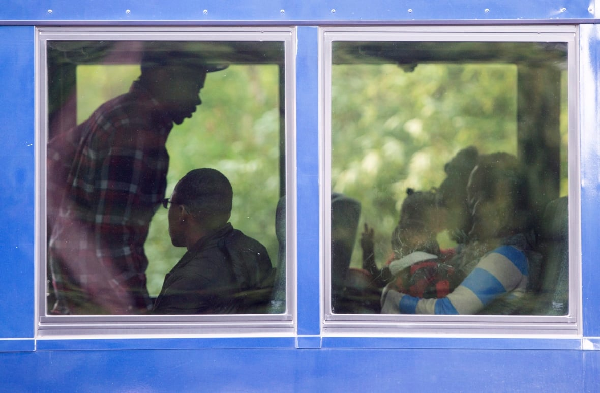 Asylum seekers are seen on board a bus after crossing the border into Canada from the United States at a police checkpoint near Hemmingford, Que. (Paul Chiasson/Canadian Press)