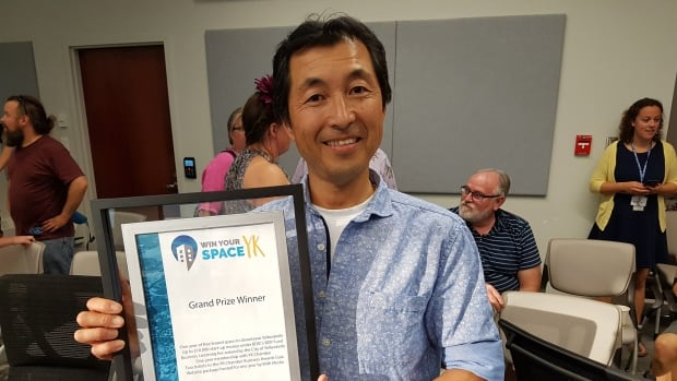 Seiji Suzuki holds up his certificate announcing his win in the City of Yellowknife's Win Your Space contest Wednesday night. Suzuki won for his Japanese-style bakery idea, Ja-pain.