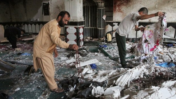 Relatives inspect the aftermath of a suicide attack at a mosque in Herat, Afghanistan, on Aug. 2.