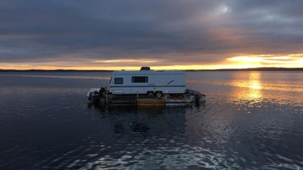 A 26-foot travel trailer floats across Notre Dame Bay on Newfoundland's northern coast Thursday. The trailer was towed by Gilbert Budgell and Kevin Hill on a makeshift floating dock by two speedboats, headed to Exploits, where it will serve as a cabin.