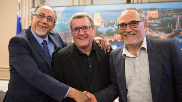 Boufeldja Benabdallah, from left to right, interim co-ordinator at the  Quebec Islamic Cultural Centre, Quebec City Mayor Régis Labeaume and Mohamed Labidi, the president of the centre, shake hands after they announced the establishment of a Muslim cemetery, at city hall in Quebec City.