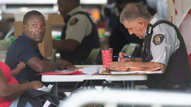An asylum seeker is processed by RCMP officers after crossing the border into Canada from Champlain, N.Y., in Hemmingford, Que., Friday, August 4, 2017.