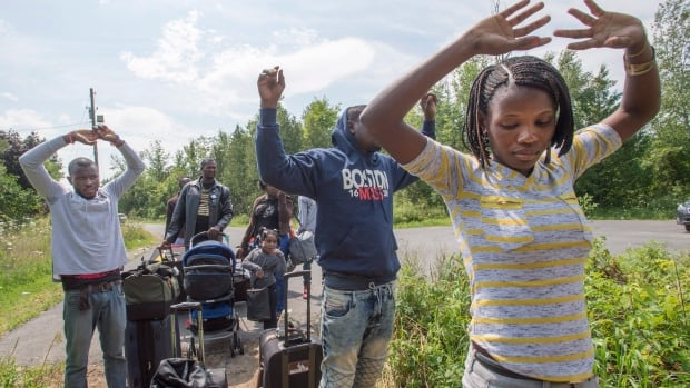 A group of asylum seekers raise their hands as they approach RCMP officers while crossing the Canadian border into Quebec near Champlain, N.Y. on Friday, Aug. 4, 2017.