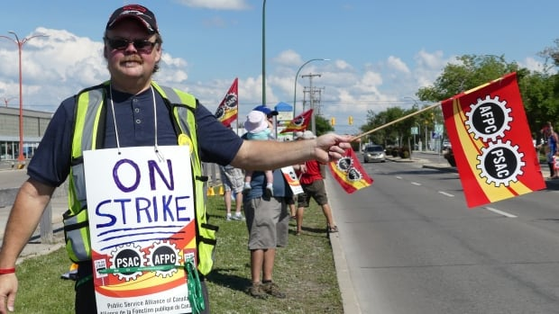 Airport employees held signs and waved flags on Wellington Avenue just before the entrance to the Richardson International Airport over the weekend. They've been on strike since July 24.