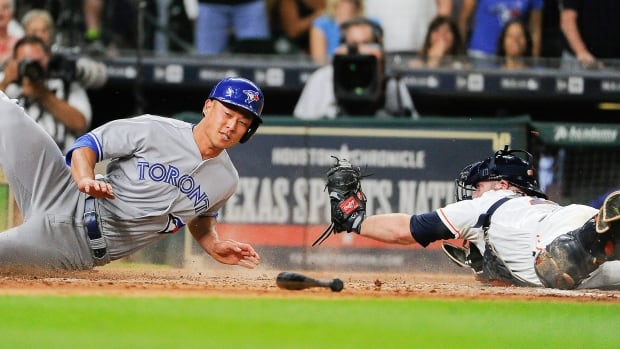 Toronto Blue Jays' Rob Refsnyder, left, slides past Houston Astros catcher Brian McCann to score the go-ahead run on Ryan Goins' single during the 10th inning of Saturday evening's game.