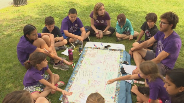 Camp founder Natalie Fletcher sits with campers as they discuss wisdom and philosophy on Concordia's Loyola Campus.
