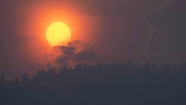 Smoke is seen rising in front of the sun as a wildfire burns near Little Fort, B.C.