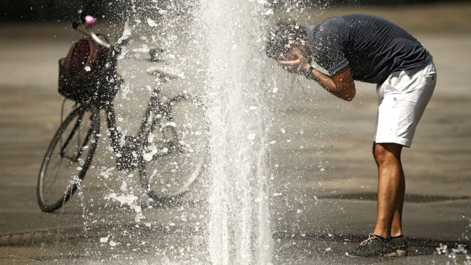 A man refreshes himself with the waters of a fountain at Turin's Piazza Castello, Aug. 2, 2017, seeking relief from a heat wave that continues to grip southern Europe.