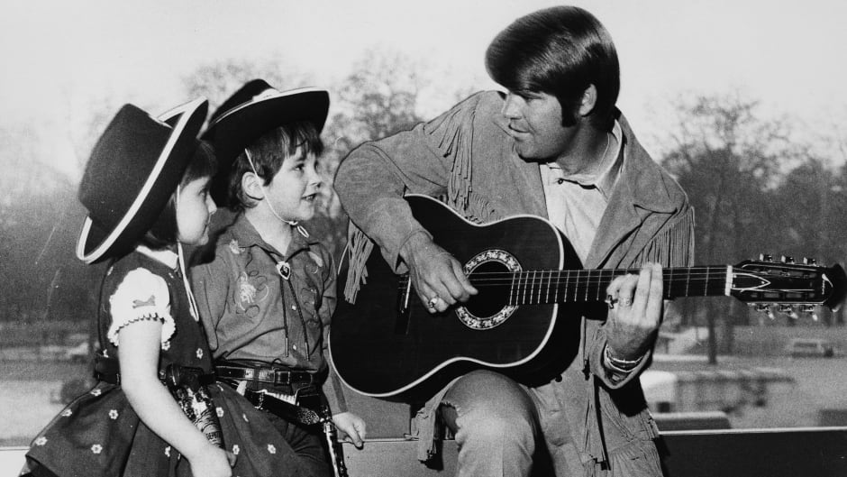 Campbell plays the guitar for two young fans, Renata Romoli and Francis Bradford, wearing cowboys hats in April 1970.