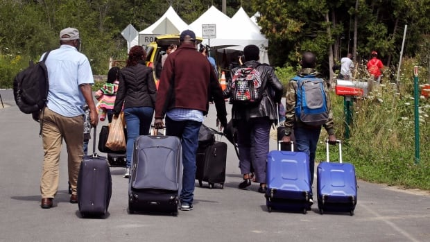 A family from Haiti haul their luggage down Roxham Road in Champlain, N.Y., earlier this week, where they crossed illegally into Quebec to claim asylum.