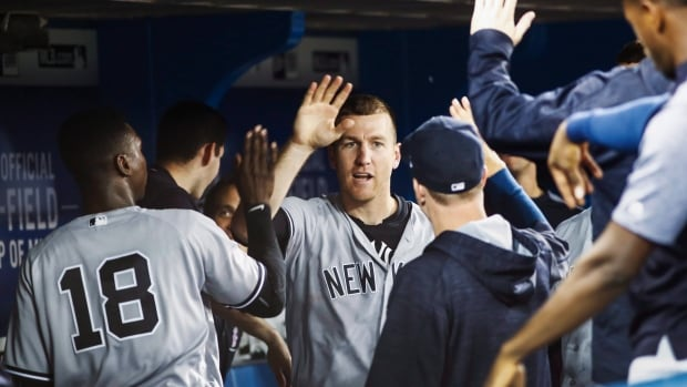 New York Yankees' Todd Frazier is congratulated by teammates after scoring against the Toronto Blue Jays.