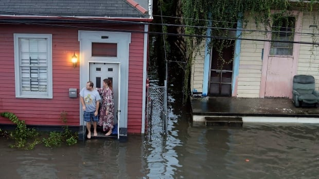 People stand in floodwaters outside their New Orleans home on Aug. 5.