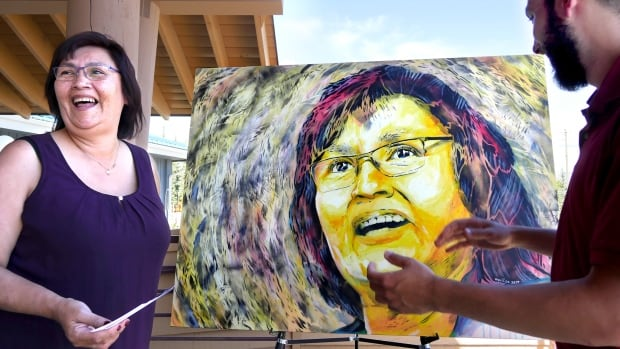 Chief Doris Bill of the  Kwanlin Dün First Nation reacts to her larger-than-life portrait, revealed by artist Aquil Virani. The painting is part of a series of 'inspiring women' says the artist.
