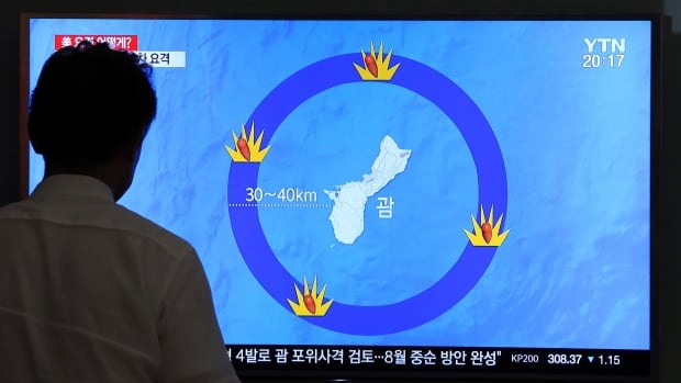 A man watches a TV screen showing a local news program reporting on North Korea's threats to strike Guam with ballistic missiles, at the Seoul Train Station in South Korea, on Thursday.
