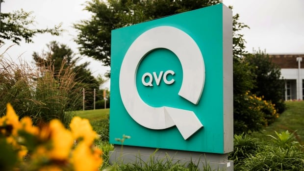A corporate sign is shown outside a QVC facility in West Chester, Pa. A former director of the home shopping network has been charged with defrauding the company out of more than $1 million U.S.