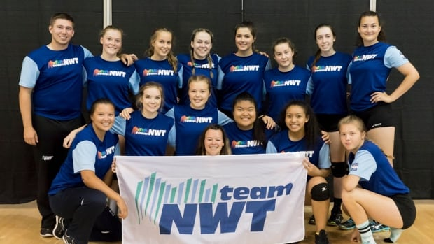 Team NWT's women's volleyball team pose in their uniforms. The altered, rainbow logos are seen on the players shirts, while the traditional logo is on the team's flag.