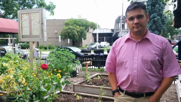 Christopher Adam, executive director of St. Joseph's Parish, stands next to the community garden that was damaged by vandalism over the August long weekend.