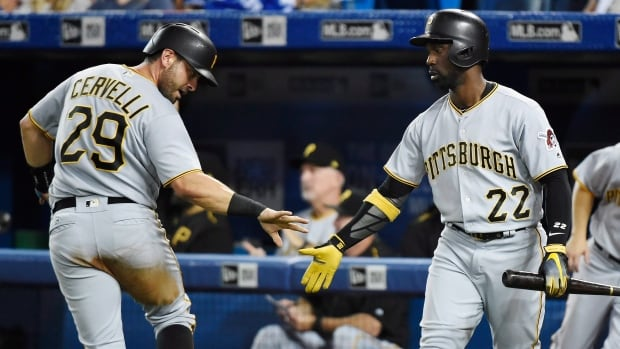 Francisco Cervelli, left, scores one of four unearned run for the Pirates in the fourth inning as Pittsburgh defeated Toronto 4-2 on Friday.