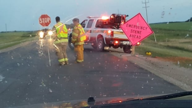 Emergency crews directing traffic after a car went up in flames in the ditch next to Hwy. 18 south of Hwy. 2 on Friday.