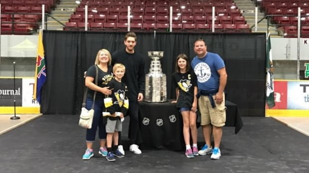 Tena Enge and her family pose with homegrown National Hockey League star Matt Murray and the Stanley Cup.