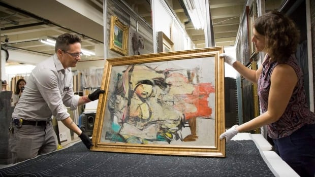 Willem de Kooning's Woman-Ochre is readied for examination by Nathan Saxton, right, an exhibitions specialist, and Kristen Schmidt, a registrar, in Phoenix after the painting was stolen 30 years prior and recently discovered.