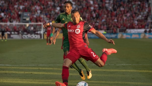 Toronto FC's Justin Morrow scores his team's first goal as Portland Timbers' Alvas Powell trails during second half.