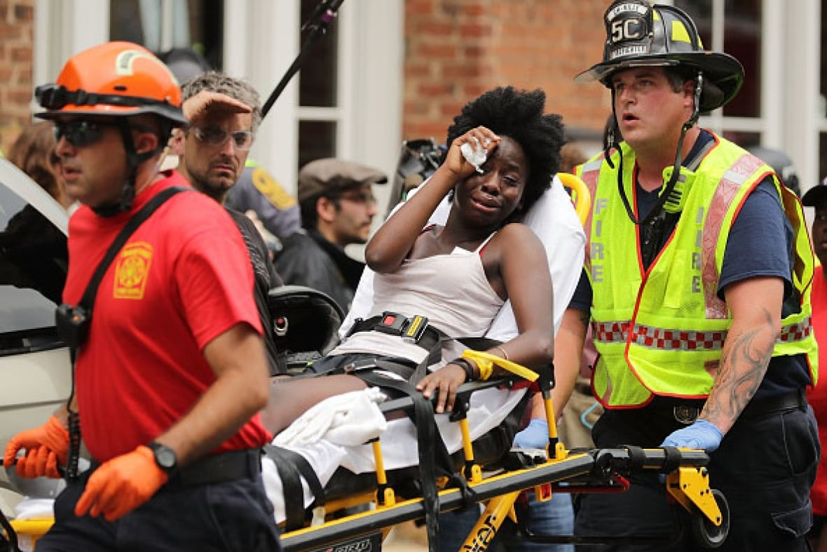 Rescue workers move victims on stretchers after a car plowed through a crowd of counter-demonstrators marching through the downtown shopping district of Charlottesville, Va. (Chip Somodevilla/Getty Images)