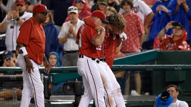 Washington Nationals' Bryce Harper, second from right, is helped off the field after he was injured during the first inning against the San Francisco Giants on Saturday in Washington.