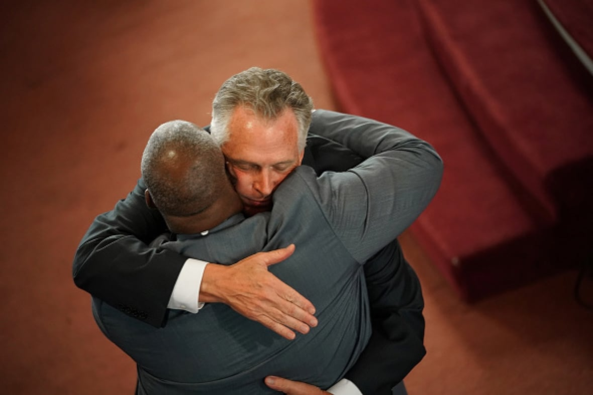 Virginia Gov. Terry McAuliffe embraces one of the worshippers at the First Baptist Church in Charlottesville after speaking at morning services. (Win McNamee/Getty Images)